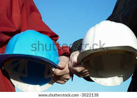two hard-hats ( focus on hand of man) - stock photo