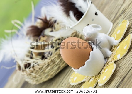 Two Hard or Soft Boiled Brown Eggs in Egg Cups Next to Basket of Eggs with Feathers on Wooden Surface in Easter Image - stock photo