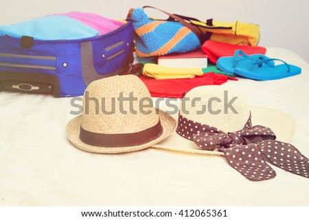 two hats and suitcase with clothing on bed in room - stock photo