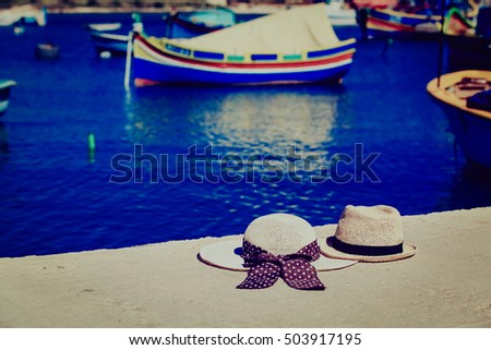 two hats with traditional maltese boats on background, travel in Malta