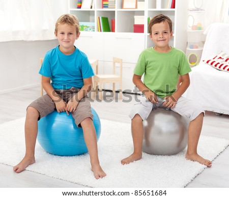 Two healthy boys playing in their room with large gymnastic balls - stock photo
