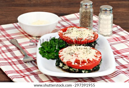 Two healthy portabella mushrooms pizzettas with spinach, tomato and mozzarella cheese. - stock photo