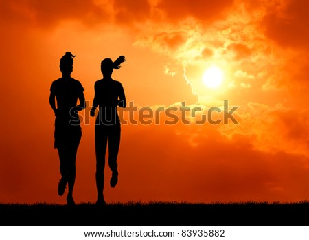 two healthy woman run together at sunrise silhouetted - stock photo