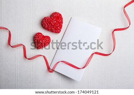Two heart-shaped candles, empty postcard and red ribbon with a p