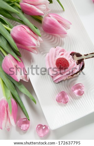 Two heart shaped chocolate cups deserts filled with raspberry cream and garnished with fresh raspberry. Desert for Valentine Day. Bouquet of spring pink tulips and candles.
