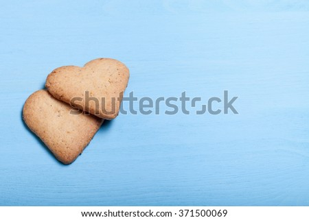 Two heart-shaped cookie on a blue wooden table.