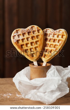 Two heart shaped golden waffles on a stick in a ceramic pot. - stock photo