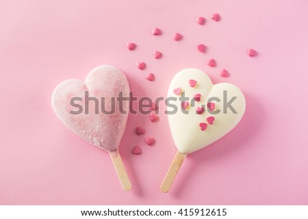 Two heart-shaped ice cream covered with confetti on pink background - stock photo