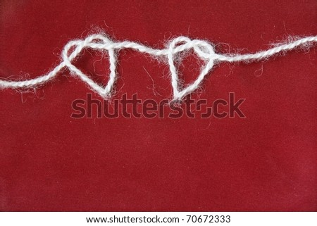 Two heart shapes from knitting yarn against dark red textile - stock photo