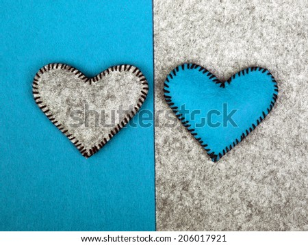 two hearts: blue and gray on two different backgrounds, as a symbol of fitting in a relationship - valentine concept - stock photo