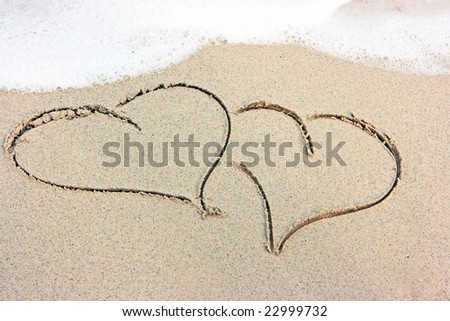 Two hearts drawing on the sandy beach