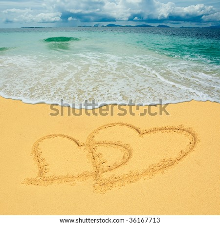 two hearts drawn in a sandy tropical beach