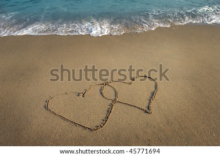 two hearts drawn in beach