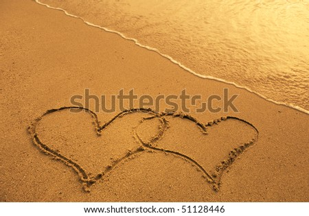 two hearts drawn in beach - stock photo