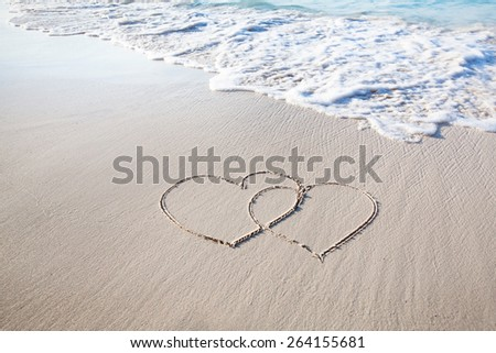 two hearts drawn on perfectly white sand of paradise beach - stock photo