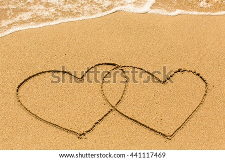 Two hearts drawn on the beach sand.
