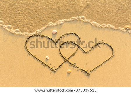 Two hearts drawn on the sand of a beach. - stock photo