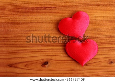 Two hearts for Valentine's day on warm wood grain cedar background - stock photo