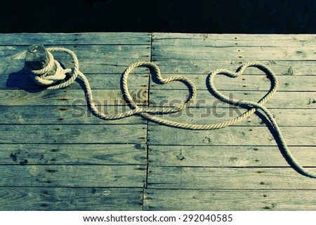 Two hearts from a rough rope on a textural wooden pier against the sea. Two hearts from a sea rope. Valentine's Day card - stock photo
