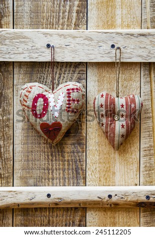 Two  hearts hanging over rustic wooden background. Symbol of love. Greeting card for wedding, engagement or Valentine's day