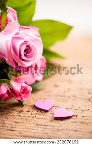 two hearts in front of a bouquet of roses - stock photo