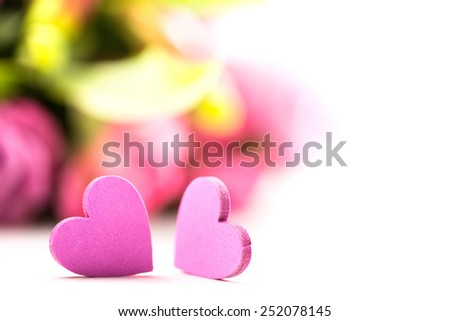 two hearts in front of roses on isolated background - stock photo