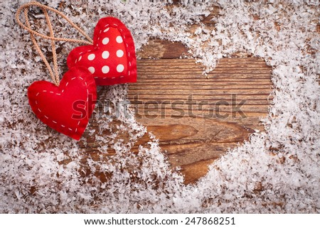 Two hearts of handmade cloth on wooden background in the snow. Wedding invitation. Card for Valentines - stock photo