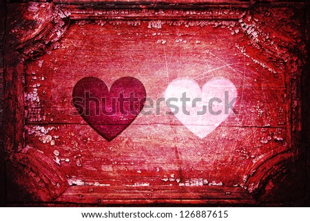 Two hearts -- one red, one 'missing' white -- inside an old red wooden frame. Vivid red color with dark edges. Aged rough background. - stock photo