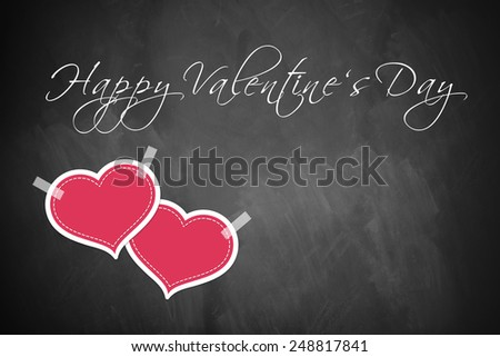 two hearts taped on a blackboard with a Happy Valentine's Day message - stock photo