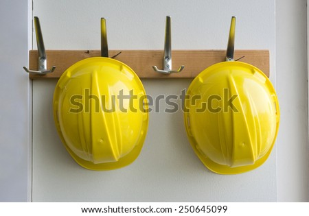 Two helmets hanging on coat hangers on a construction place - stock photo