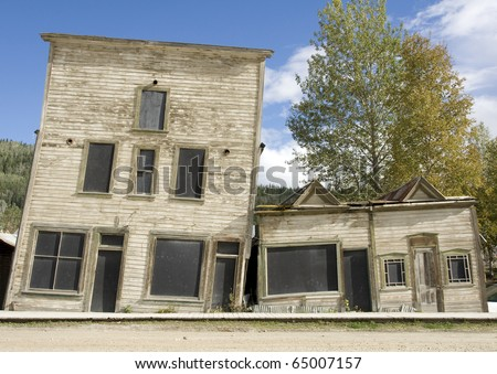 Two heritage buildings in Dawson city, Yukon, slant towards each other due to melted permafrost - stock photo