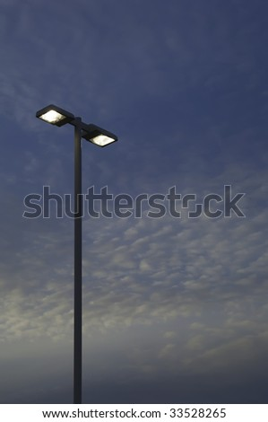Two high outdoor lights against evening sky - stock photo