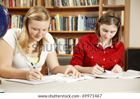 Two high school students doing their homework in the library. - stock photo