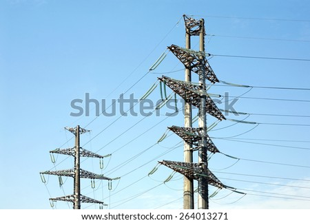 Two high-voltage power line grey metal props with many wires vertical view over clear cloudless blue sky bottom-up view - stock photo