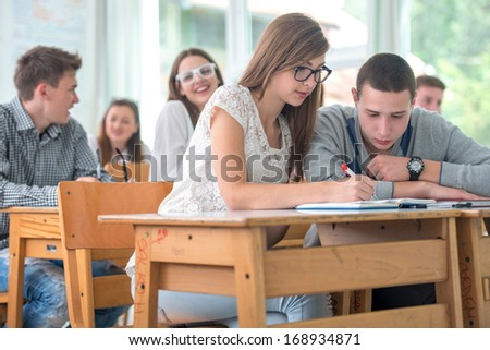 Two highschool students studying together in classroom - stock photo