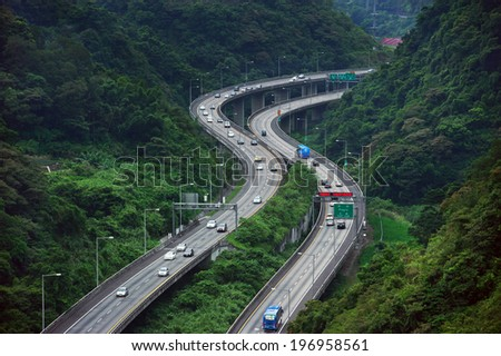 Two highways full of cars near a forest covered mountain. - stock photo