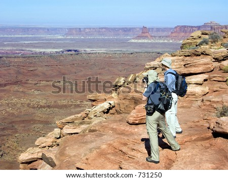 Two hikers admire the vista from Island in the Sky; Canyonlands National Park - stock photo