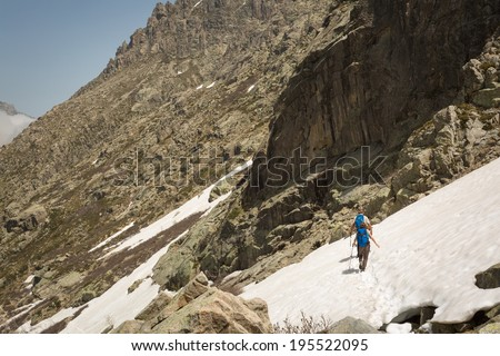 Two hikers and two dogs traversing the snow in the mountains of Restonica near Lac de Melo