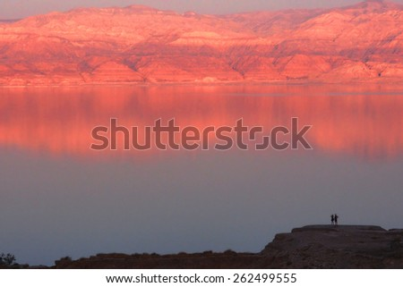 Two hikers appreciating the view of the Dead Sea, in a peaceful yet vibrant dusk. - stock photo