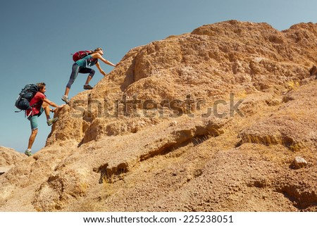 Two hikers crossing rocky terrain in the desert at sunny day - stock photo