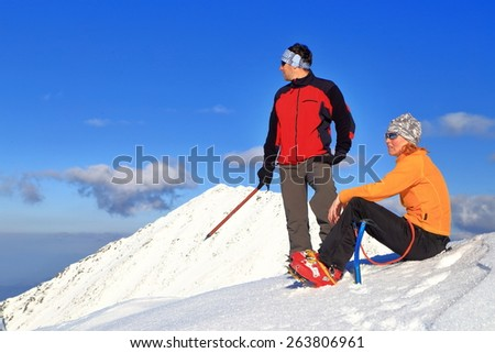 Two hikers equipped with ice axes and crampons resting and enjoying the view from snow covered summit  - stock photo