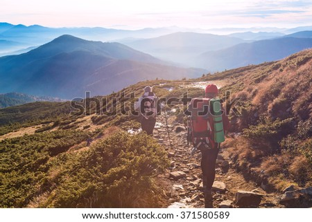 Two Hikers Man and Woman sportive Family walking along Mountains grassy Trail Scenic View of stacked smoky Ridges and Evening Sunlight on Background - stock photo