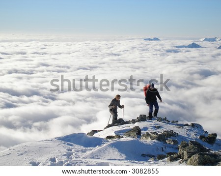 Two hikers on top of peak - stock photo
