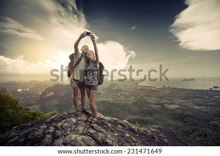 Two hikers taking selfie from top of the mountain with valley view on the background - stock photo