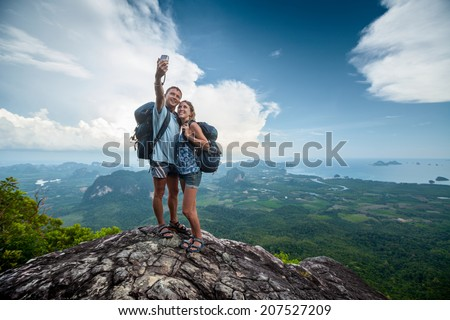 Two hikers taking selfie on top of the mountain - stock photo
