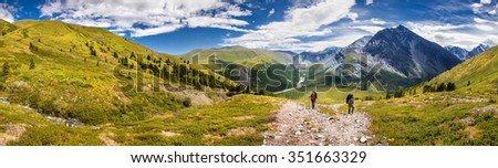 Two hikers walk along a trail in the altai mountains - stock photo