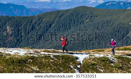 Two Hikers walking along Mountain Crest Bright Colors sporty Clothing Backpacks and trekking Poles Hills covered by green Forest on Background - stock photo