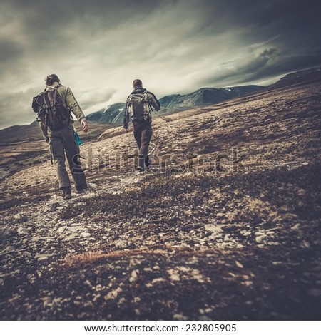 Two hikers walking in a valley