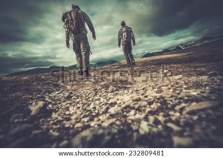 Two hikers walking in a valley  - stock photo