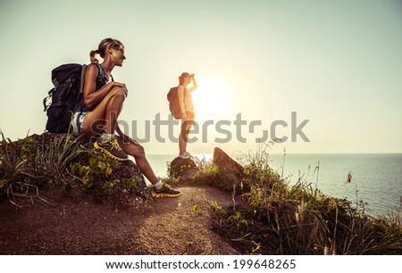 Two hikers with backpacks relaxing on a rocky hill and enjoying sunset - stock photo